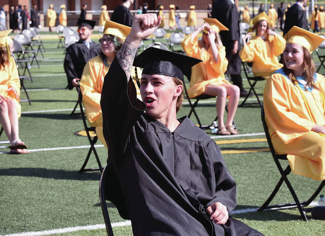 Jonathan Scott Farmer puts up his fist as he shouts towards people in the stands during the Sidney High School annual commencement at Sidney Memorial Stadium on Saturday, June 20. Chairs were distanced and people attending was limited to help prevent the spread of COVID-19.