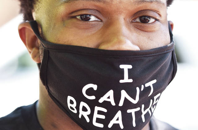 """Jalen Hudgins, of Piqua, wears a face mask with the words """"I can't breathe"""" on as he walks around the courtsquare with a group demonstrating against the death of George Floyd on Sunday, June 7. At 2 p.m.. Floyd said """"I can't breath"""" while a Minneapolis police officer kneeled on his neck."""