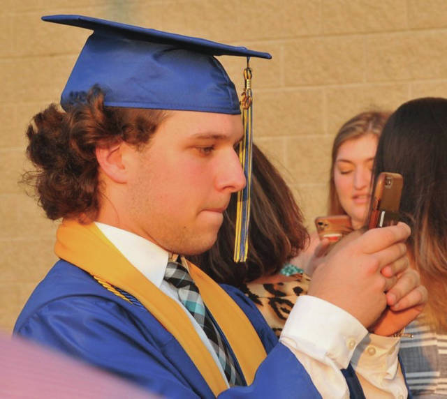 RJ Bertini gets ready to post a selfie of his cap and gown during the Lehman Catholic High School graduation ceremony on Friday, June 26.