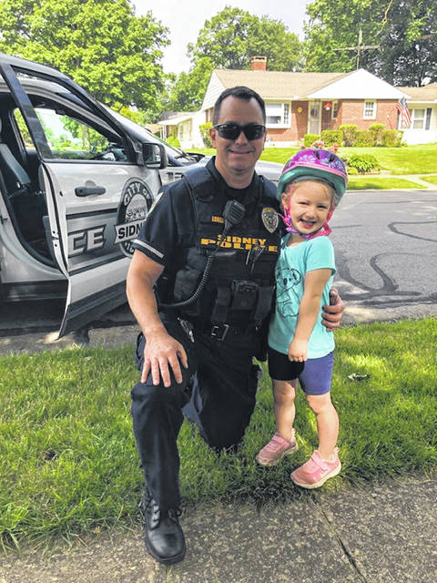 Sidney Police Officer Jeremy Lorenzo issues a ticket to a child wearing a helmet while she was riding a bicycle.