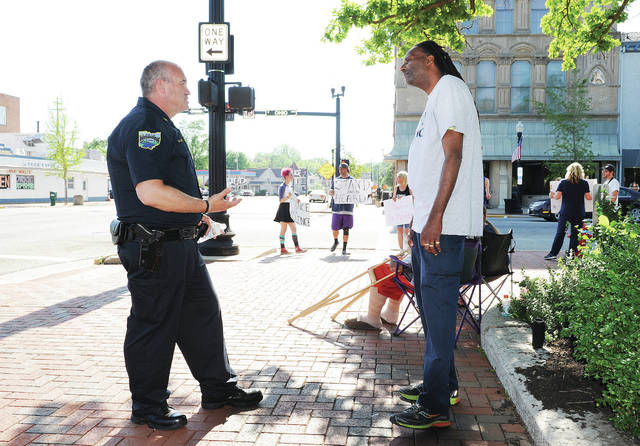 "Sidney Police Chief William Balling, left, talks with William Suttle, of Sidney, on the courtsquare where people were protesting the death of George Floyd on Tuesday, June 2. Balling said he didn't like the term ""protesting"" he said ""What I see here is people demonstrating and working towards a solution."" When asked if he was a protester Suttle said ""I'm a part of the movement."" Balling said he was planning on coming down and talking with the demonstrators on as many days as he could."