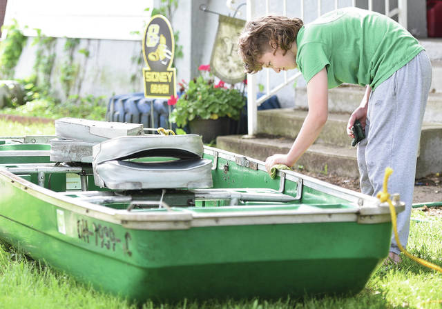 Draven Ferguson, 11, of Sidney, son of Andrew and Kelly Ferguson, scrubs down a boat in his front yard on North Street so his dad can use it to fish with a friend.