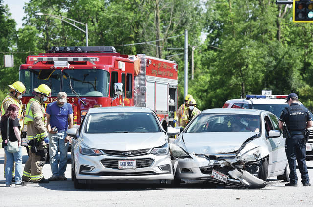 Sidney Firefighters and Police respond to a two-vehicle crash at the intersection of West Court Street and Fourth Avenue shortly before 4 p.m. on Friday, June 5.