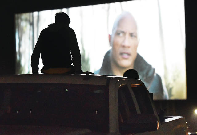People sit on a pickup truck as they watch Jumanji The Next Level at the Sidney Auto-Vue Drive-In Theatre on Friday, June 5. Friday was the drive-in's season opening. The drive-in has a table setup against the concession door so people can pick-up their food without going into the building helping to prevent the spread of COVID-19. Vehicles are also being spread apart.