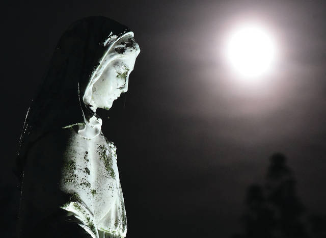 A statue of Mother Mary stands under a strawberry moon in front of Lehman Catholic High School on Friday, June 5.