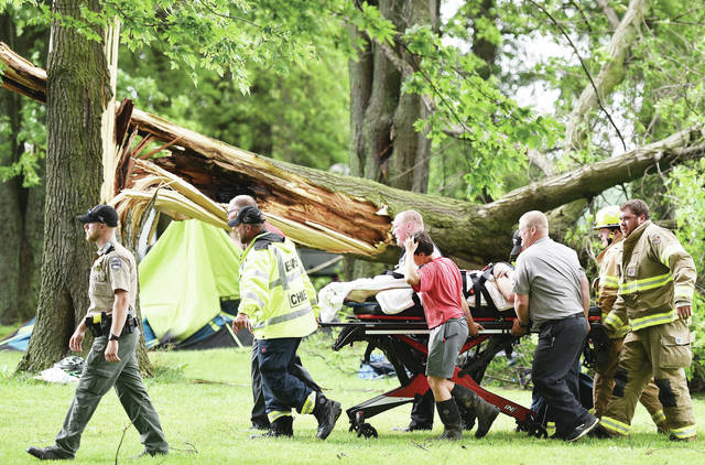 Fort Loramie firefighters and rescue workers push a man on a stretcher past the tree that he had been trapped under at Lake Loramie State Campground around 4:45 p.m. on Wednesday, June 10. The man was loaded into an ambulance and taken to a hospital. The tree also fell on a tent. A number of large trees were knocked down at Lake Loramie State Park after a short but strong storm went through the area. A section of state Route 29 was blocked off just north of Sidney after the top section of an electric pole was left hanging over the road when it was snapped in half by the storm. Hundreds of people in Shelby County were without power from the storm.