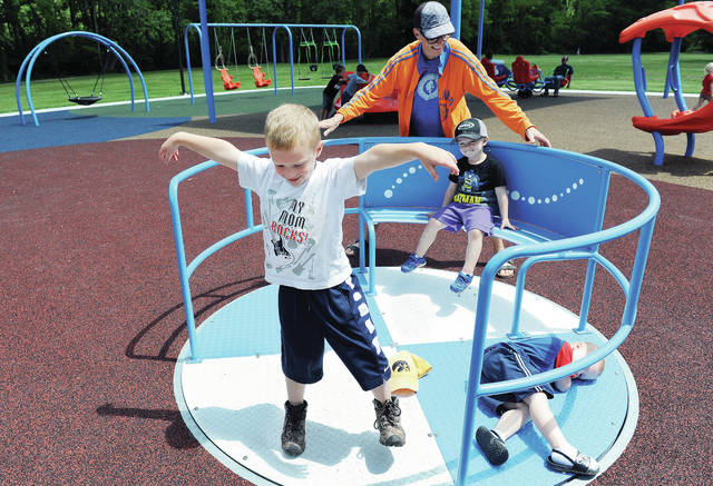 Ann Weiskittel, of Sidney, pushes her grandsons around on a piece of playground equipment at the Kiwanis-Rotary All Inclusive Park at Tawawa Park on Thursday, June 11. Ann and her husband Jack Weiskittel had the boys for the day. The boys, left to right, are Barrett Watson, 5, Sawyer Watson, 3, and Lincoln Watson, 3, all of Clayton, all the children of Sam and Abby Watson. Ann said they take their grandchildren to the park a lot and the boys were happy that the City of Sidney had reopened the playground equipment.