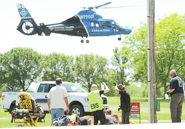 Careflight lands as Sidney Fire Department rescue workers and Lockington firefighters work on a man who sustained serious injuries when his motorcycle crashed after a pickup truck pulling a trailer pulled into the motorcycle's path as the motorcycle was coming over a blind hill on Millcreek Road just west of its intersection with Kuther Road around 2:30 p.m. Friday, June 12. The Shelby County Sheriff's Office is investigating the accident.