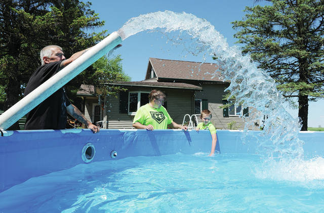"""Having their swimming pool filled with water on Thursday, June 11, are, left to right, Bob and Lisa Ferguson and their son Colten Ferguson, 9, all of Sidney. The family employed Gene Steinke, of Troy, who owns """"H2O To Go"""" to fill up their pool with fresh water. The Ferguson family has owned the above ground swimming pool for 2 years. The family lives on County Road 25A near the Sidney Airport. As soon as the pool was filled Colten jumped in."""