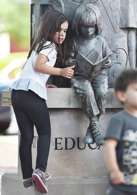 Mia Myers, 6, of Troy, daughter of Matt and Heather Myers, looks at a sculpture on the courtsquare during a cruise organized by the Shelby County Historical Society on Saturday, June 13.