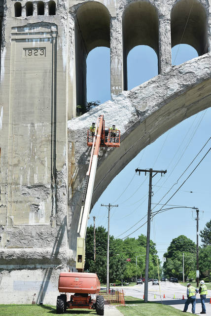 CSX employees scrape off loose concrete and then apply a sealer on the Big Four Bridge over a section of sidewalk on the west side of S Main Avenue. The sidewalk under the bridge has been closed due to falling pieces of concrete. The workers plan to reopen the sidewalk after they are done.