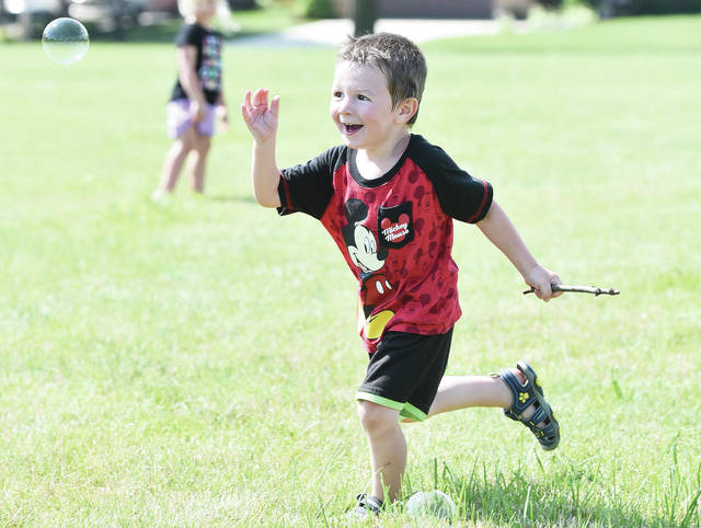 Dax Taylor, 3, of Sidney, son of Stephanie Henman, chases down a bubble while in a field near the Sidney-Shelby County YMCA on Tuesday, June 30. Dax was taking part in some outdoor playtime while enrolled in the YMCA Child Development Center.
