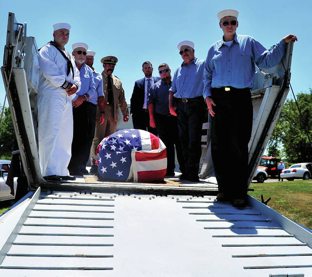 Relatives, many dressed in World War II re-enactors uniforms, serve as pallbearers, prepare to carry the casket of family patriarch Marion Adams to his final resting place at Miami Memorial Park on Wednesday. Adams, a United States Navy veteran of World War II, participated in the D-Day landings at Normandy on June 6, 1944, as a Signalman aboard LST-491. He carried a life-long love for his country and the military, which he instilled in his children and grandchildren.