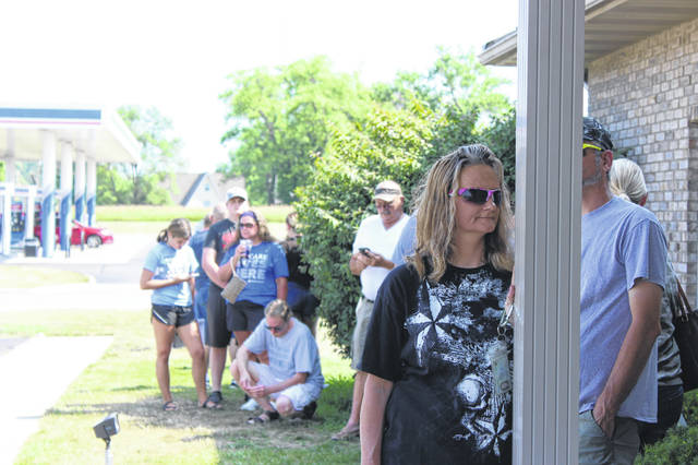 Angie Steiner, of Botkins, waits at the front of the line outside the Sidney Bureau of Motor Vehicles on Monday, June 6. Steiner had been waiting in line for 40 minutes before being allowed to enter the BMV due to the limit of nine customers allowed in the building at a time.
