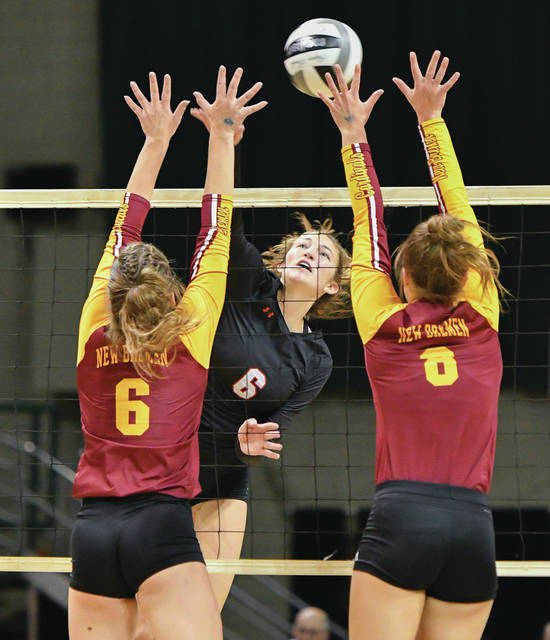 Fort Loramie junior middle hitter McKenzie Hoelscher spikes as New Bremen's Taylor Paul, left, and Macy Puthoff try to block during the Division IV state championship volleyball match on Nov. 9, 2019, at Wright State University's Nutter Center. The Ohio High School Athletic Association is proceeding as if fall sports will occur will this year.