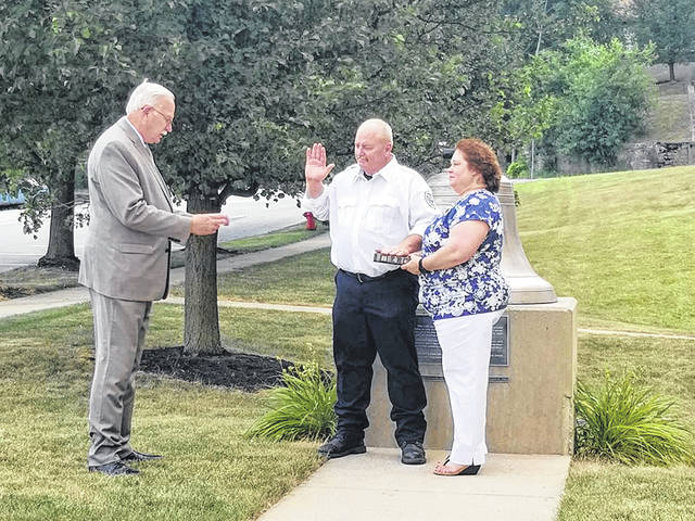 Mayor Mike Barhorst swears-in Sidney fire lieutenant Mark Barga, with wife Lorri by his side, Monday, July 6, as the Sidney Department of Fire & Emergency Services's newest assistant fire chief. Barga was sworn in out front of Sidney Fire Station No. 1.