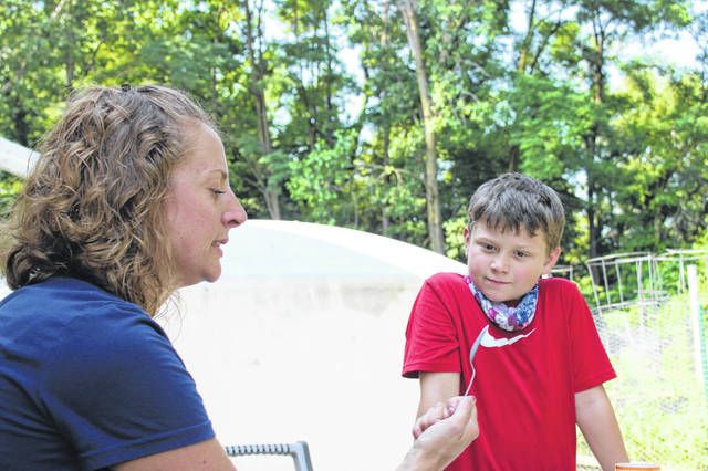Dillon Brown, 9, son of Morgan and John Moormon Jr., of Sidney, listens as Sophie Nieport explains how to make a marker to put in plants so that they can be differentiated from weeds in a garden. At Thursday's session of the Kid's Summer Garden Series held at the People's Garden, participants dug compost and got to take home planters that they planted seeds in.