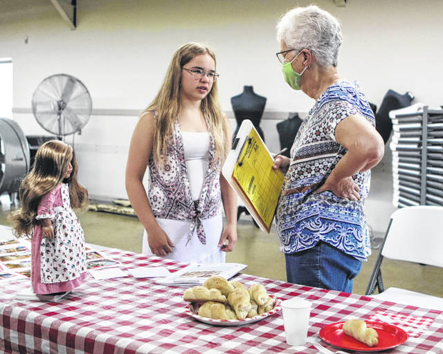 "Amy Briggs, 14, daughter of Judy and Mark Briggs, of Sidney, talks with Judge Sally Dicke, of New Bremen, about her ""On the Rise"" yeast bread project during 4-H judging Monday at the Shelby County Fairgrounds. Amy is a member of Merry Mod Makers 4-H Club. This is her third year of entering the category."