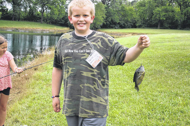 Jacob Berning, son of Ben and Becky Berning, of Anna, holds a fish he caught while attending the Shelby County Conservation Day Camp June 23 and 24.