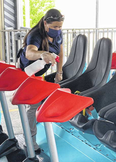 A Kings Island associate sanitizes the seats on Orion to help prevent the spread of infection during the media preview for Orion on July 1.