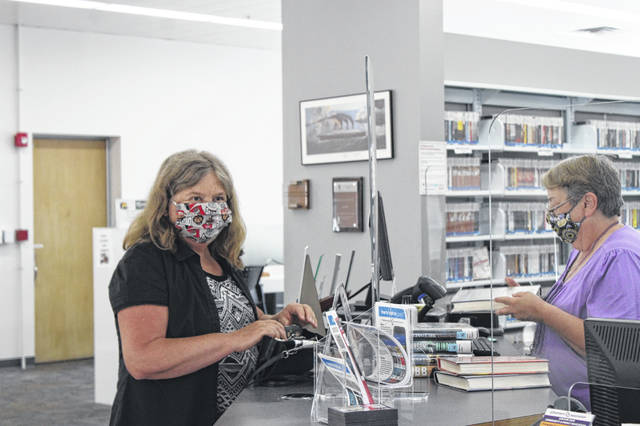 Jeanie Thoma, left, of Sidney, checks out a stack of books at the circulation desk of Amos Memorial Library on Monday morning. Thoma was one of the first patrons to visit the library when it reopened Monday. Her favorite genres of books are romance and detective stories, and some of her favorite authors are James Patterson, Danielle Steel and Nicholas Sparks.