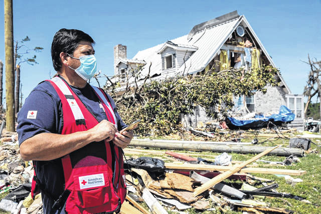 A volunteer with the American Red Cross assesses tornado damage.
