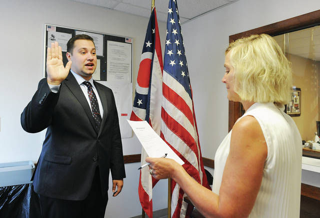 Collin Claywell, left, of Vandalia, is sworn in as the Shelby County Board of Elections Deputy Director by Shelby County Board of Elections Director Pam Kerrigan, of Sidney, at the Shelby County Board of Elections office on Wednesday, July 1.