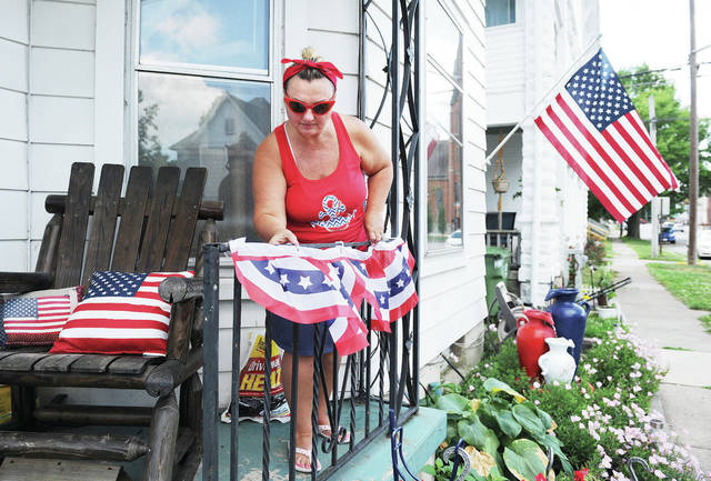 """Kathleen Pruitt, of Sidney, adjusts bunting on her porch along Water Street on Thursday, July 2. Pruitt has decorated her porch in patriotic paraphernalia such as a sign that says """"Sweet land of liberty"""" and a pillow that says """" God shed His grace on thee."""" Pruitt decorated her porch back on Monday, June 1, to send the message that in regards to fighting the coronavirus """"We're in this together as Americans."""" The festive decorations are also appropriate for the Fourth of July. Pruitt and her family will be attending the Sidney fireworks display that will be held behind the Sidney High School at 10 p.m. on Saturday, July 4. The Sidney Civic Band will perform at 9 p.m."""