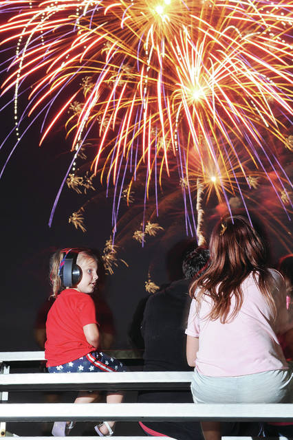 Lily Daniels, left, 4, looks over at Phylisity Daniels, 12, both of Sidney, both the children of Heather and Coleman Daniels, while they watch the Sidney fireworks from benches located behind the Sidney High School tennis courts on Saturday, July 4.