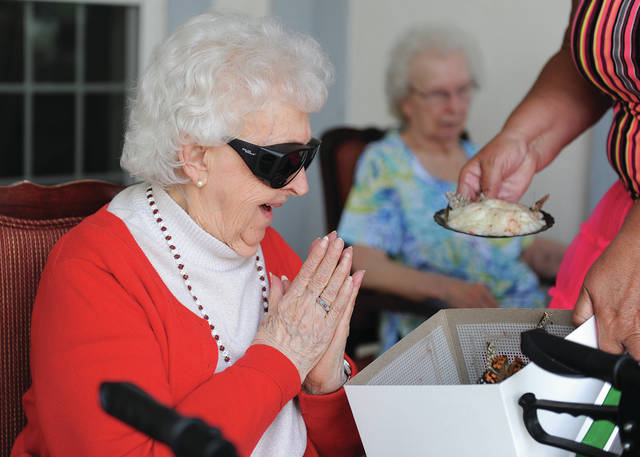 Elmwood Assisted Living resident Irene Howe reacts to a box full of butterflies held by Activities Director Margie Luedeke during the 10th anniversary week kick-off at Elmwood Assisted Living of New Bremen on Monday, July 6. New Bremen mayor Bob Parker also spoke during the event.