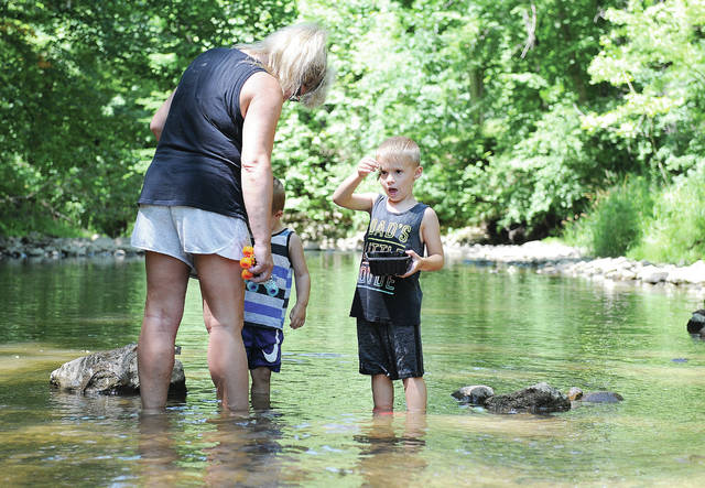 Paxton Stewart, right, 4, looks at a crayfish claw he found with his grandma Cheryl Stewart, left, and his brother Jace Stewart, 2, all of Sidney, in Mosquito Creek on Wednesday, July 15. Cheryl Stewart said they found quite a few crawdads but will probably bring a net next time. The brothers are the children of Daniel Stewart and Kirsten Barger.