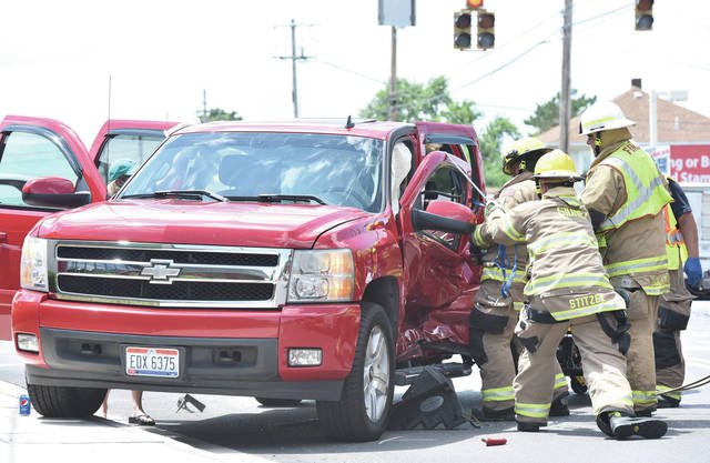 Sidney firefighters use the jaws of life to open the door of a pickup truck to free the man inside after the door was smashed in by a Jeep Grand Cherokee at the intersection of West Russell Road and Wapakoneta Ave. around 2:20 p.m. on Tuesday, July 21. The man was taken to a waiting ambulance by stretcher. The Sidney Police also responded.