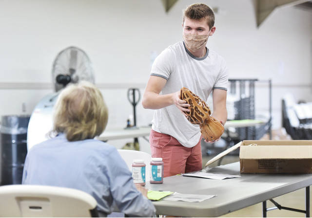 Evan Luthman, right, 18, of Fort Loramie, son of Brenda and Edward Luthman, has his giant morel mushrooms judged by Ann Asher, of Sidney, in the ceramics category during pre-fair judging at the Shelby County Fairgrounds on Wednesday, July 22.
