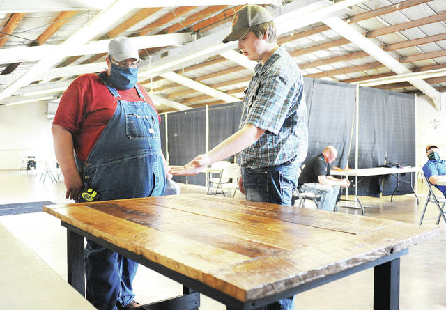 """Caleb Farrier, right, 17, son of Joshua and Haley Farrier, describes to judge Rodney Stephenson, both of Houston, how he made a farm table during Shelby County pre-fair judging at the Shelby County Fair Grounds on Friday, July 24. Farrier used old barn wood for the project which he entered in the woodworking category of """"Finishing Up."""""""
