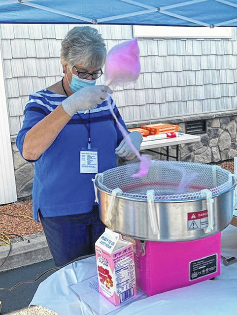 Paulette Pohlman, of Sidney, spins cotton candy during Saturday's free family event sponsored by the Cornerstone Assembly of God Saturday July 11. Families were able to enjoy free hot dogs, snow cones and popcorn.