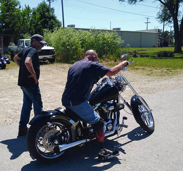 Hogg Cycle Shop owner Chris Lovett looks on as Ron Anthony sits on his modified motorcycle.