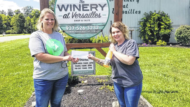 Carlena Sneed, Events Coordinator for the Versailles Winery presents Big Brothers Big Sisters Executive Director, Jennifer Bruns with the proceeds from the event.