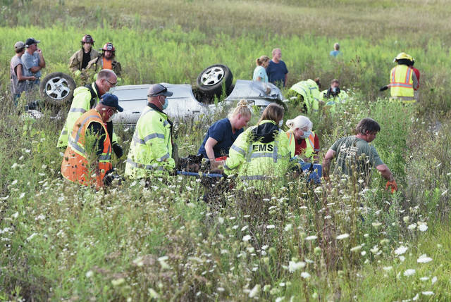 Rescue workers carry a man injured in a one vehicle crash to a waiting ambulance as another person is worked on who was also in the car that crashed around 5:40 p.m. on the 4000 block of Loramie-Washington Road. Both occupants of the car were Careflighted from the scene. Houston and Fort Loramie ambulances drove the two injured people to a nearby field where they were loaded onto the same helicopter. Houston and Lockington firefighters responded to the scene. The Shelby County Sheriff's Office is investigating the crash.