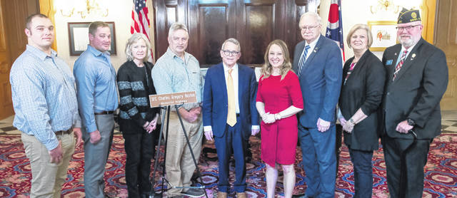 Joining Ohio Gov. Mike DeWine for a photo following the ceremony in which he signed House Bill 276 are, left to right, Rodney Huston, Greg Huston, Kristie Huston, John Huston, DeWine, Rep. Susan Manchester, Sidney Mayor Mike Barhorst, Deborah Moorman and James Moorman.