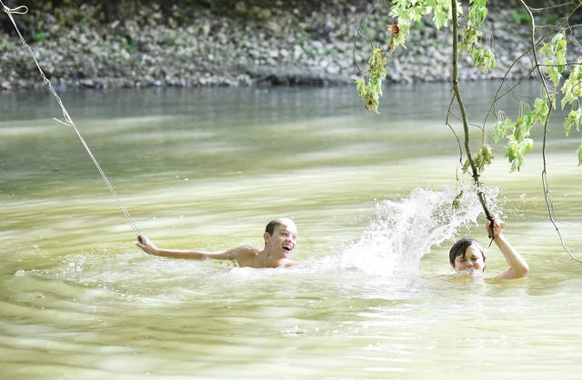 Issac Snell, left, 15, clinging to a rope suspended from a tree, splashes his brother Maliky Snell, 13, both of Sidney, as Maliky clings to a tree branch, during a trip to a swimming hole on the Great Miami River recently. The boys say they have been going to the swimming hole with their other siblings almost every day this summer. The swimming hole is located along Veteran's Memorial Walkway near Norwood Avenue. Both brothers are the children of Amanda Snell and Christopher Haley,