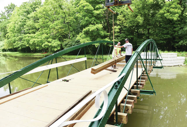 Steve Laing, left, of Defiance, and Erick Lowe, of Belle Center, guide a load of boards over the historic 1875 Zenus King bowstring bridge being installed over Amos Lake on Tuesday, Aug. 11. The wood being used to cover the bridge is southern yellow pine. A protective railing also will be installed on the bridge to prevent people from falling off. Next concrete ramps leading up to either side of the bridge will be installed.