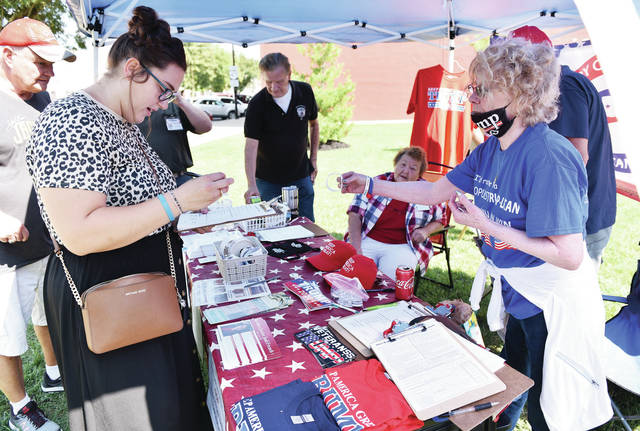Ariel Huffman, left, signs a Trump campaign volunteer interest and merchandise form as Shelby County Republican Party Campaign Chairman HR Pence, both of Sidney, offers a Trump wrist band to her under the Shelby County Republican Party campaign headquarters tent. The Republican Campaign headquarters was set-up next to the Gay Smith real estate office at 216 E. Poplar St. on Saturday, Aug. 15.