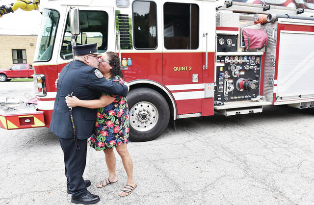 Sidney firefighter Doug Stammen, left, kisses his wife Robin Stammen, both of Sidney, shortly after Stammen's retirement ceremony from the Sidney Fire Department after 29 years in the department. After the ceremony at Station 1 Stammen was driven to a retirement party on Quint 2. Both Stammen's dad, Hershel Couch and grandpa Chester Steed were firefighters.