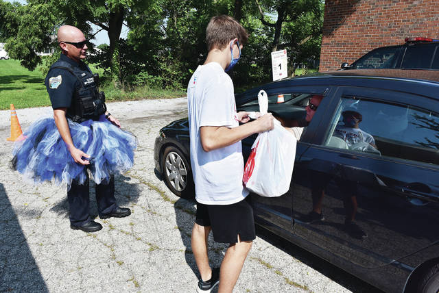 Sidney Police Officer Bryce Stewart, left to right, helps direct cars as Evan Myers, 16, of Sidney, son of Kara and Doug Myers, prepares to put back-to-school supplies into the car of Pat McGovern, all of Sidney, as McGovern picked the supplies up for his grandkids. The supplies were handed out by the The Sidney/Shelby County Salvation Army in its parking lot to prevent possible exposure to COVID-19 on Saturday, Aug. 15. The event was organized by Salvation Army Capt. Katie Mayes. Also helping was Shelby County Sheriff's DARE Officer Brian Strunk and kids under the care of Community Service Coordinator Tabitha Bales.
