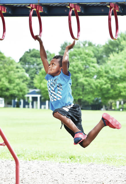 Jahmir White, 7, of Anna, son of Jodi Greve, swings his way around a jungle gym at Deam Park while taking part in the Sidney-Shelby County YMCA Summer Camp on Tuesday, Aug. 18.