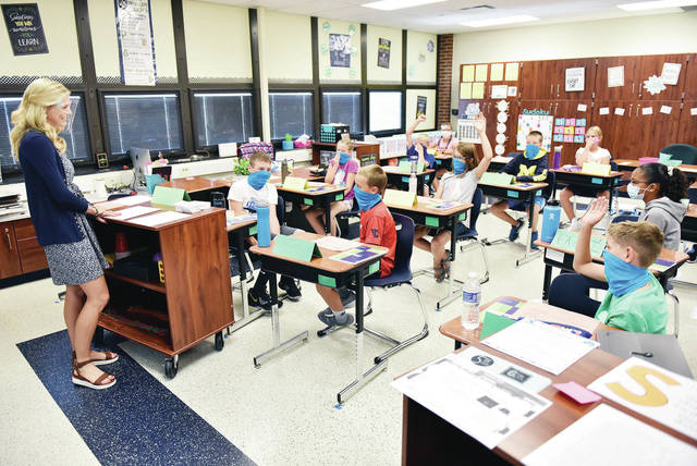 Elizabeth Knapke, far left, of Versailles, listens as her Russia fifth-grade students take turns describing what they did for their summer vacations during their first day back to school on Wednesday, Aug. 19. All the students in the class are wearing masks while Knapke is wearing a face shield.