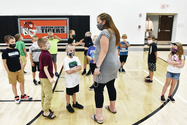 Amanda Barhorst, of Maplewood, talks with her first grade class as they wait to leave the main Jackson Center Local Schools gym after an orientation talk. It was their first day of school on Thursday, Aug. 20.