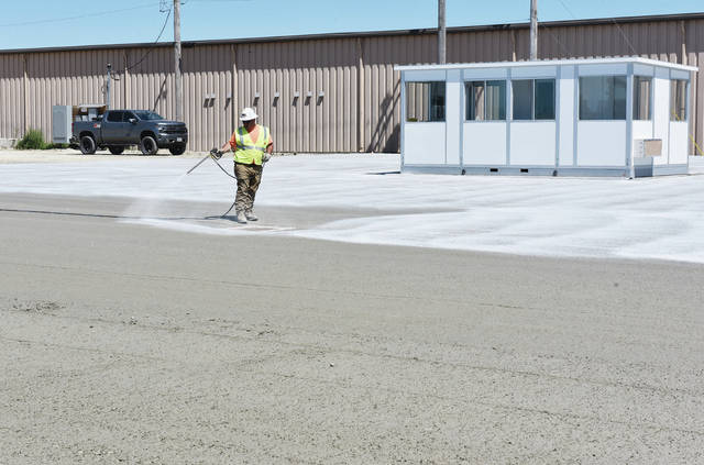 Steve Hoon, of Columbus, sprays concrete curing compound on a new parking lot along Industrial Drive next to Cargill on Thursday, August 20. The curing compound will prevent moisture from leaving the concrete to quickly as it dries and it will help reflect sunlight to keep the concrete from getting too hot. The parking lot will be used by trucks delivering harvest to Cargill.
