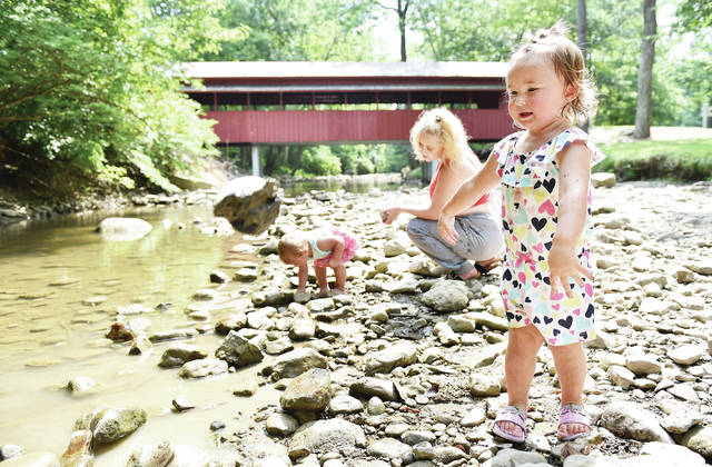 Amara Selanders, far right, 2, daughter of Jennifer and Doug Selanders, tosses a rock into Tawawa Creek while on a playdate with Addison Brewer, far left, 1, daughter of Wendy and Travis Brewer, at Tawawa Park on Wednesday, Aug. 26. Looking after the two kids was Madalynn Brewer, center, all of Sidney.