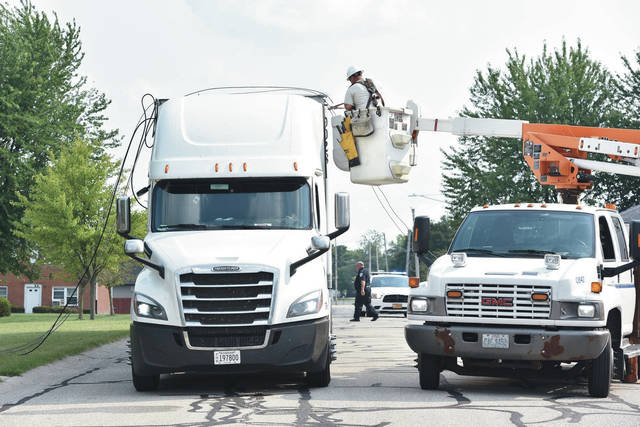 A DP&L worker cuts cables off of the top of a semitrailer on Huber Street near its intersection with East Lynn Street in Botkins on Wednesday, Aug. 26 shortly before 4 p.m. Driving north on Huber Street the semitrailer became entangled in the low hanging electric and telephone wires pulling down a utility pole and snapping a large branch from a tree. The driver of the semi trailer waited in the trucks cab until it was safe to leave. The Botkins Police and Botkins Fire Department responded to the scene.